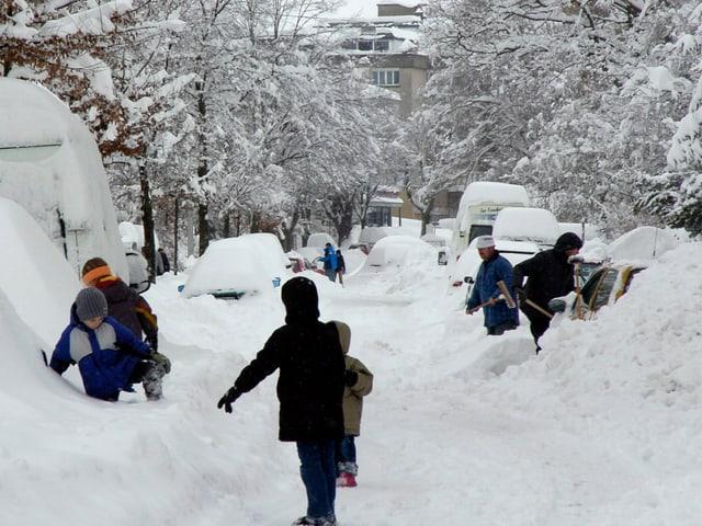 Tief verschneites St. Gallen und Menschen beim Schneeschaufeln.
