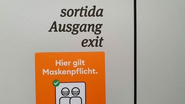 Plakat an einem Ausgang weist auf die Maskenpflicht hin