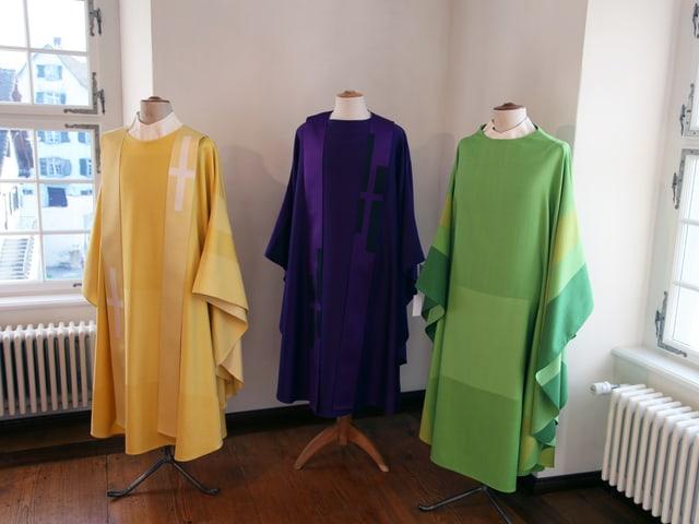 Auf dem Bild sind drei liturgische Gewänder ausgestellt. Ein Gelbes, ein Violettes sowie ein Grünes.