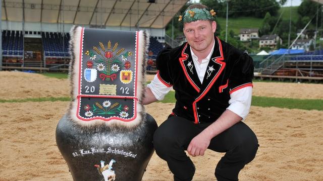 Ueli Banz kniet neben einer Kuhglocke.