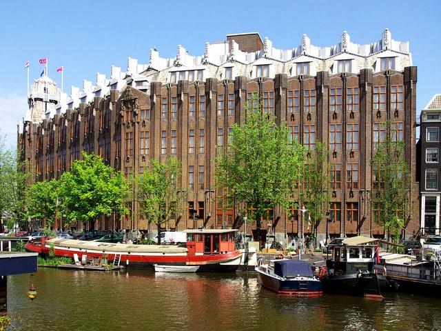 Ein grosses Gebäude mit weissen Spitzen, davor Boote.