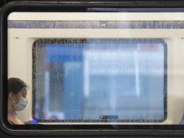 Frau mit Mundschutz in S-Bahn