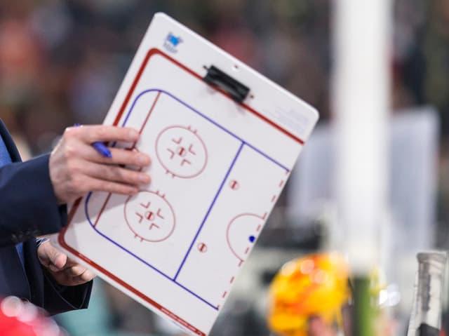 Ein Trainer hält eine Spielfeldmappe