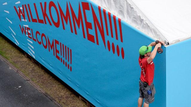Volunteers der Leichtathletik-EM hängen Plakate mit der Aufschrift «Willkommen» auf.