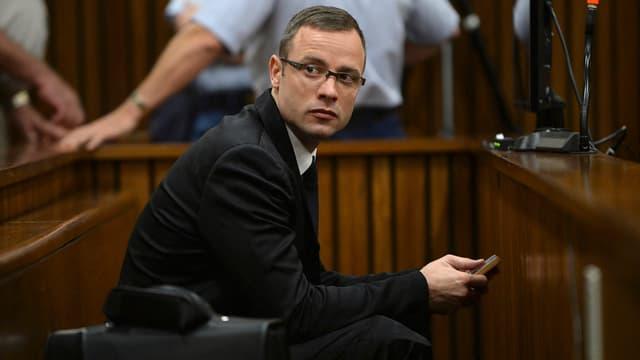 Pistorius in dunklem Anzug mit Brille sitzt im Gericht, schaut ins Publikum.