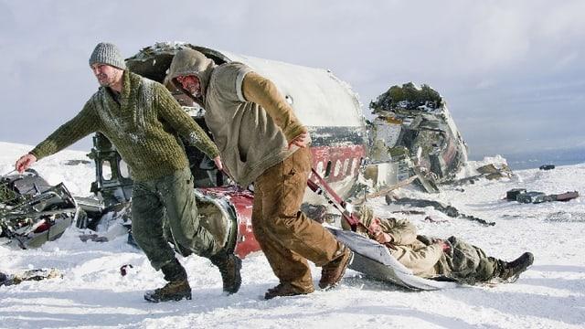 Zwei Männer ziehen einen verletzten Mann auf einer Plane durch den Schnee, dahinter ist ein Flugzeugwrack zu sehen.