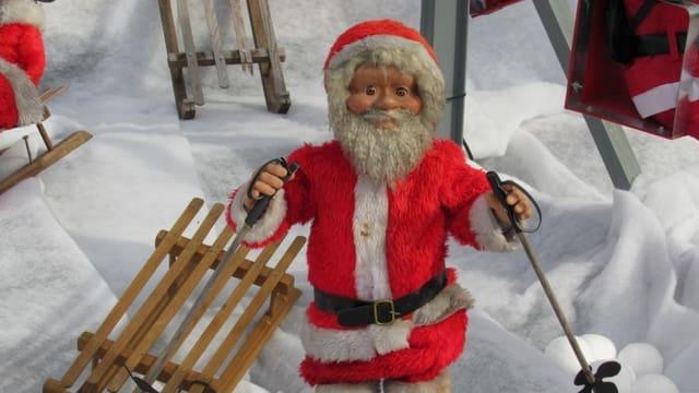 Eine Samichlaus-Puppe vor einem Holzschlitten.