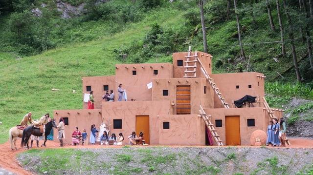 Ein nachgebautes Lehmhaus für ein Freilichttheater. Dahiner Bäume und eine steile Wiese.