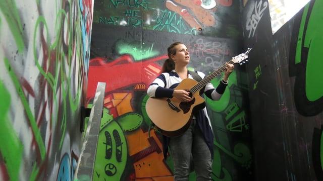 Nadja Limacher spielt Gitarre vor einer bunt besprayten Wand.