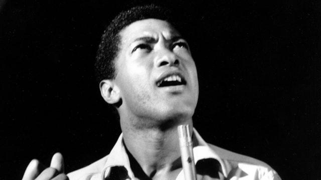 Ein junger Schwarzer spricht in ein Mikrophon, mit den Augen Richtung Himmel schauend.