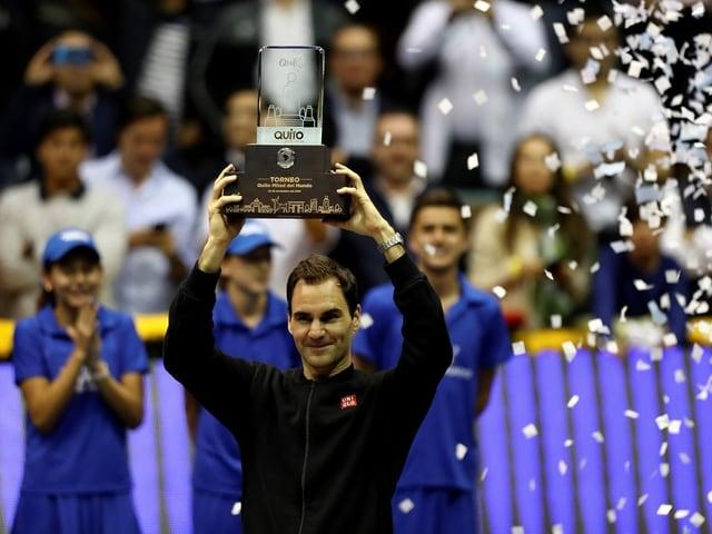 Federer posiert mit einer Trophäe.