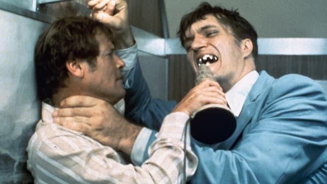 Zwei Männer kämpfen. Einer davon versucht, den anderen mit seinen Zähnen aus Metall zu beissen.