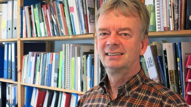 Porträt von Christoph Wiedmer vor einem Bücherregal.