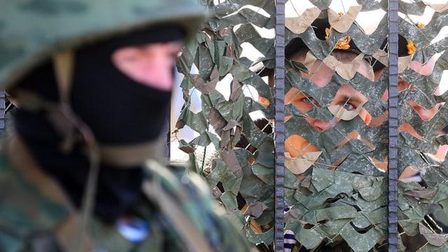Ein Vermummter steht vor einem Gitter, dahinter blicken zwei Uniformierte nach draussen.
