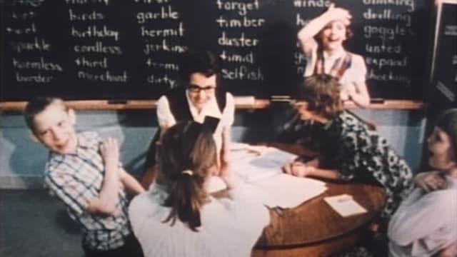Kinder und Lehrerin sitzen um Tisch