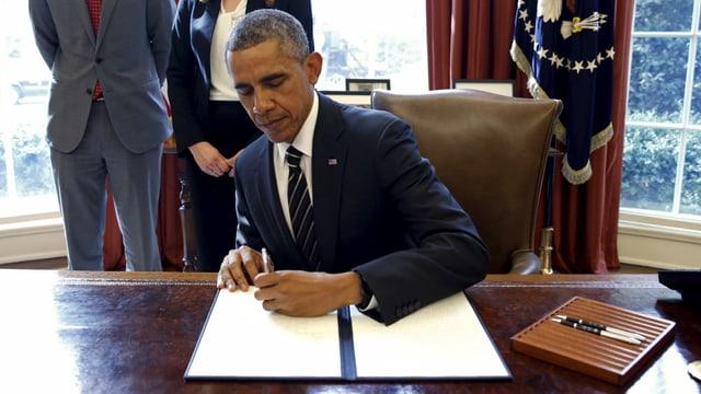 Barack Obama unterzeichnet an einem Schreibtisch ein Dekret.