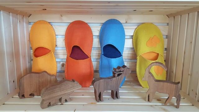 4 pantoflas da filz en orandsch, cotschen, blau e mellan e davant 4 bestgas da lain, in urs, in luf, in tschierv ed in capricorn.