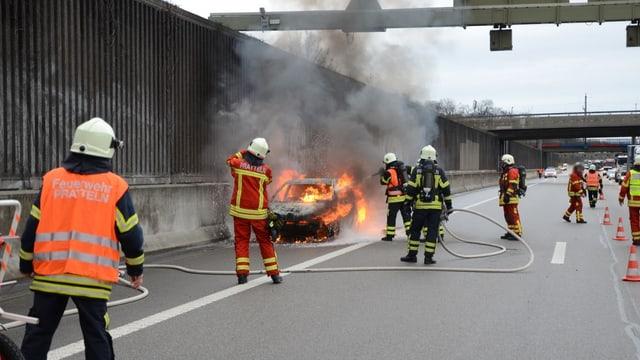 Ein Fahrzeug brennt auf der Autobahn A2, ein halbes Dutzende Feuerwehrleute löschen den Brand.