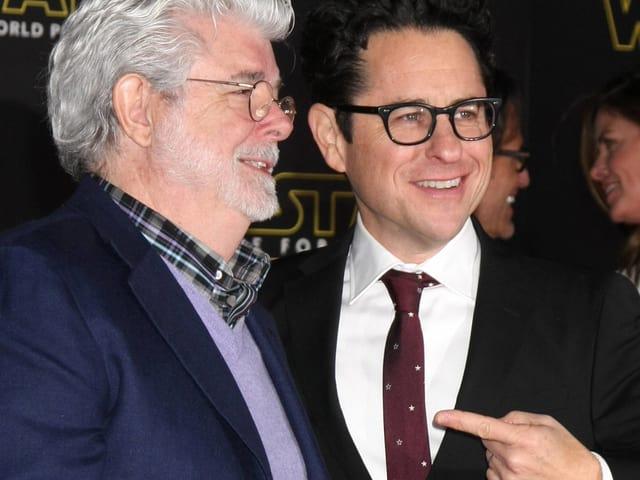 George Lucas und JJ Abrams auf dem Roten Teppich. Letzterer zeigt andächtig mit dem Finger auf sein Vorbild Lucas.