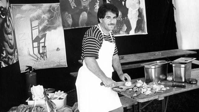 Ein Mann schneidet Zwiebeln in einem Festivalzelt.