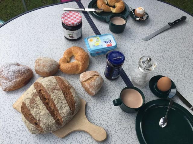 Campingtisch voller Brötchen, Kaffeetasse mit Kaffe, Salz, Eier, Konfitüre. Alles eher ungeordnet.