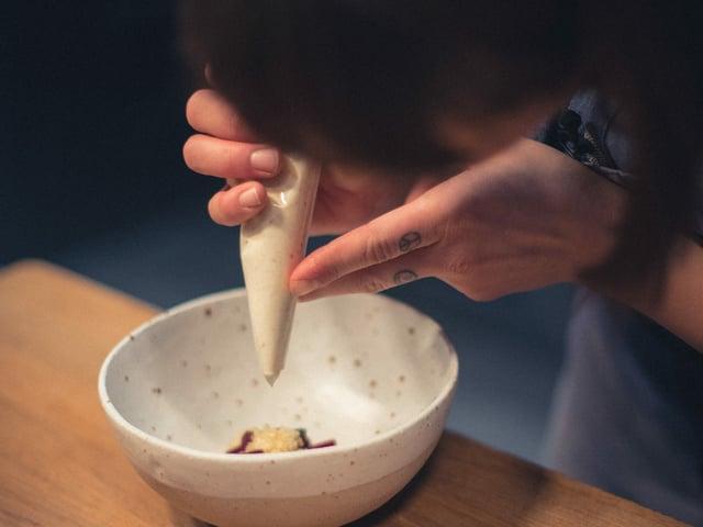 Eine weisse Masse wird in einer Spritztüte über einem Gericht gehalten.