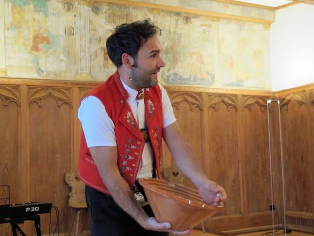 Marcel Koller mit einer Tonschüssel in der er gleich einen Taler schwingt.