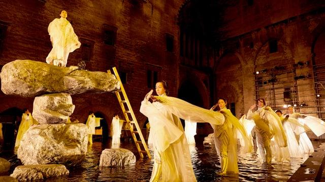 Mehrere Menschen waten durchs Wasser. Neben ihnen steht eine Frau auf einem Steinturm.