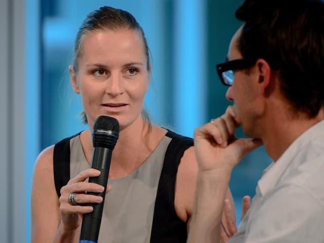 Adriana Lettrari spricht mit dem Mikrophon zu jemandem.