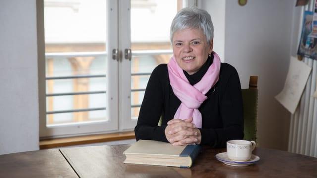 Eine Frau sitzt an einem Tisch. Ihre verschränkten Händen liegen auf einem Buch.