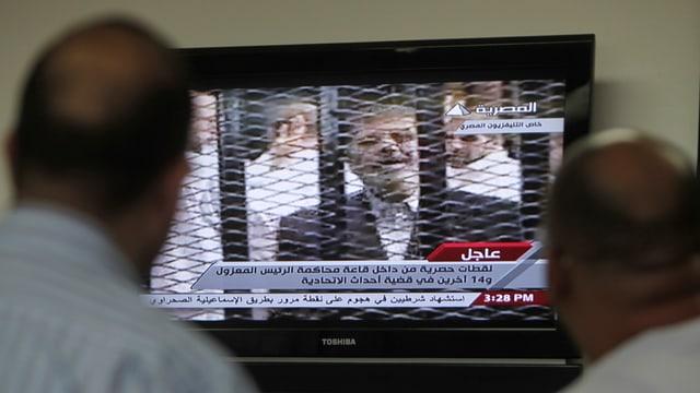 Zwei Männer schauen TV, auf dem Mursi hinter Gittern zu sehen ist