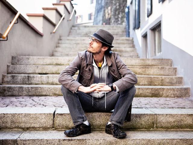 Ciacun Caduff sitzt auf einer Treppe und schaut in die Weite.