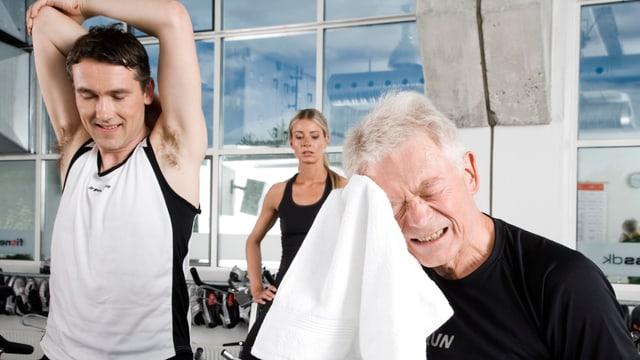 Ein jüngerer und ein älterer, sich den Schweiss abrocknenden Herr im Fitnessstudio.