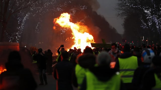 Demonstranten, im Hintergrund steigt Rauch und Feuer auf.