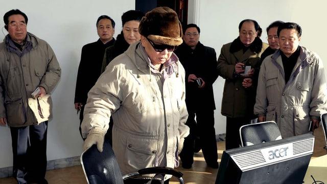 Der ehemalige nordkoreanische Diktator Kim-Jong-Il schaut auf einen Desktop – dahinter stehen mehrere Männer