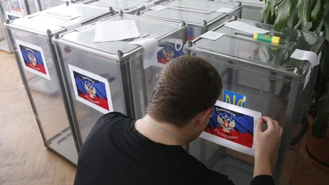 Ein Mann fertigt Wahlurnen an.