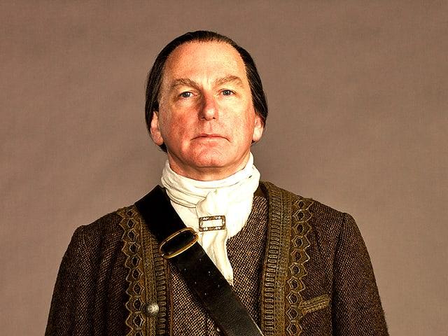 Ein Mann mit dunkeln Haaren und Uniform.