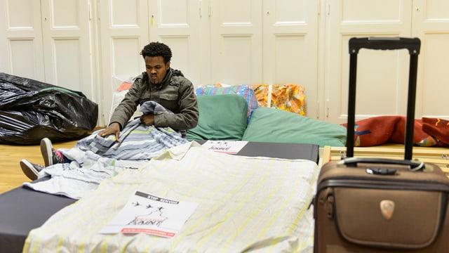 Ein Asylbewerber aus Eritrea sitzt auf einer Matratze und liest Zeitung.