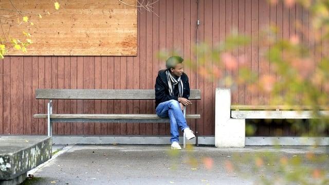 Symbolbild Asylunterkunft. Ein Mann sitz vor einer Asylunterkunft auf einer Bank.