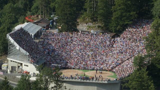 Eine bis auf den letzten Platz besetzte Arena in den Bergen.