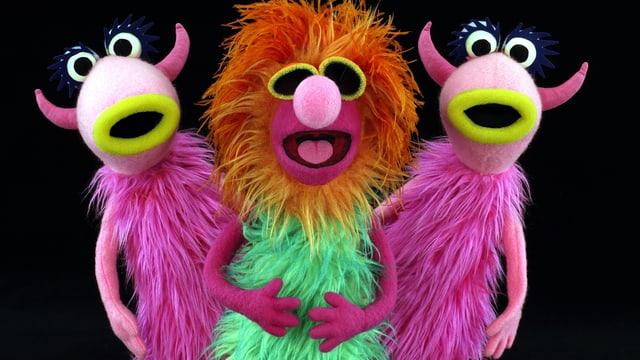 Drei haarige Muppets in einer Reihe. Sie singen.