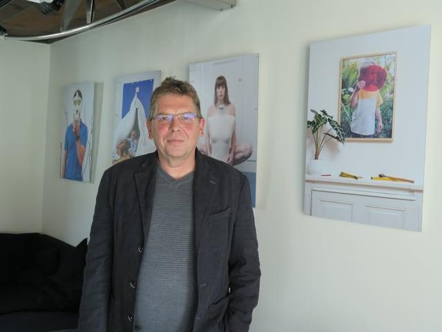 Mann steht vor Wand mit Bildern