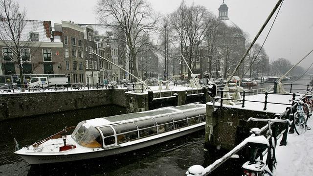 Touristenboot in Gracht fahrend in Amsterdam