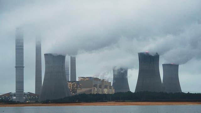 Ein Kohlekraftwerk in den USA mit acht rauchenden Kaminen, grauer Himmel, im Vordergrund ein Fluss.