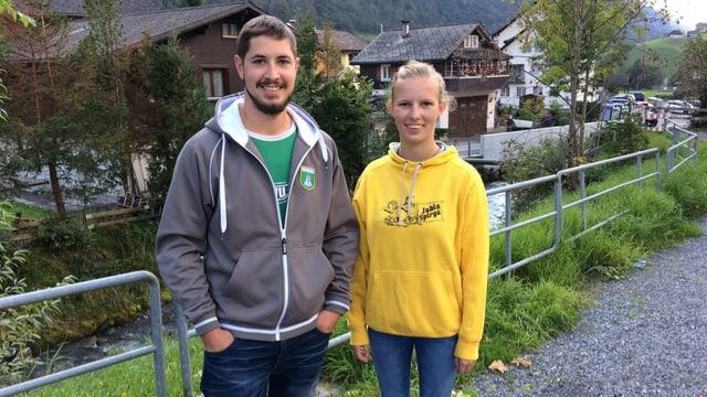 Ein junger Mann mit Bart steht neben einer jungen Frau mit einem gelben Pullover.