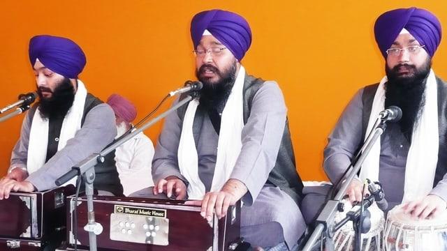 Drei Männer mit Turban singen und spielen Instrumente.