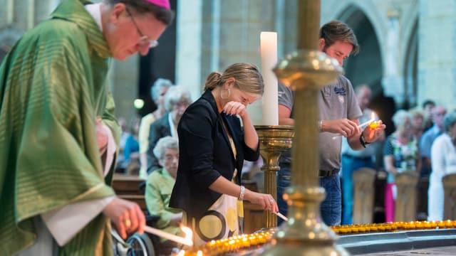 Trauernde zünden Kerzen an, die um einen Brunnen aufgereiht sind.
