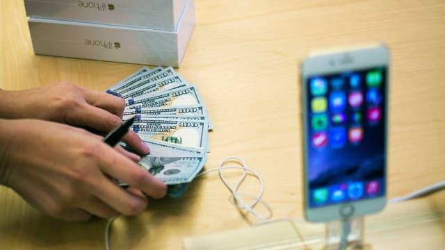Iphone im Vordergrund, ein Apple-Mitarbeiter zählt Geld.