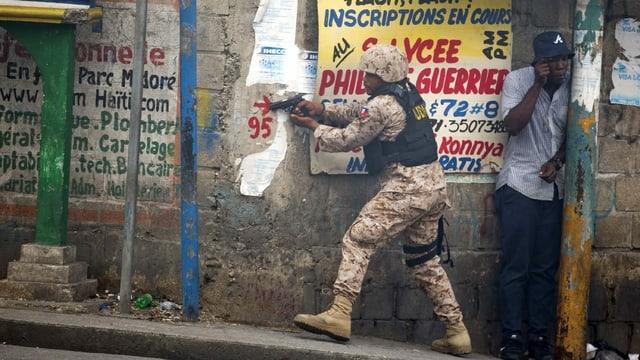 Ein haitianischer Polizist schiesst während einer Demonstration.