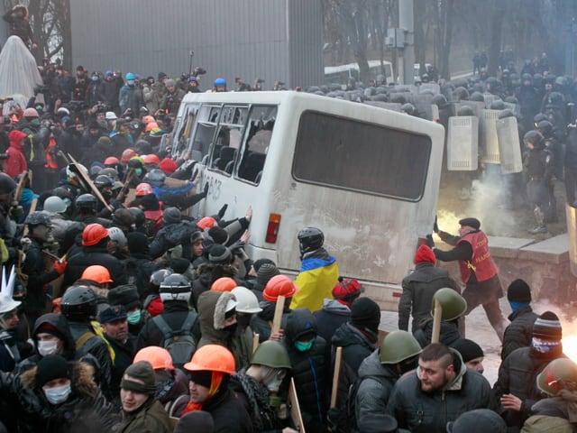Demonstranten greifen Polizeibus an.